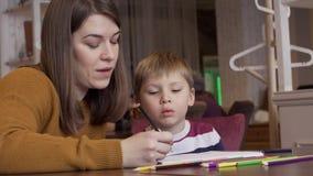La mamá muestra a su hijo curioso lindo cómo dibujar animales correctamente metrajes