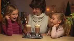 La mamá pone la tabla una bandeja con las tazas de chocolate caliente metrajes