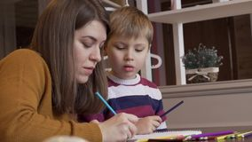 La mamá positiva muestra a su hijo cómo dibujar correctamente almacen de metraje de vídeo