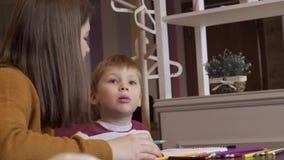 La mamá positiva muestra a su hijo cómo dibujar correctamente almacen de video
