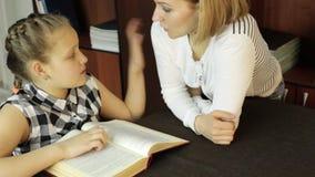 La mamá que ayuda a su hija hace la preparación la colegiala hace lecciones almacen de video