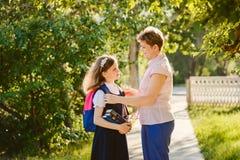 La mamá recoge a su hija a la escuela imagen de archivo libre de regalías