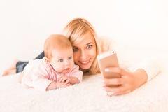 La mamá rubia hermosa y su bebé de la hija hacen el selfie en el teléfono móvil imagen de archivo