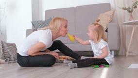 La mamá rubia joven atractiva infla un globo para su hija encantadora que se sienta cerca del sofá Pasatiempo de la familia almacen de metraje de vídeo