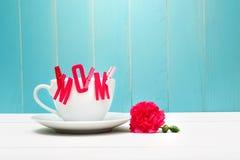 La MAMÁ sentía letras con las pinzas en la taza de café con el clavel Imagenes de archivo