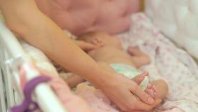 La mamá toca el durmiente en la arena del bebé El bebé tuerce en el tacto de su madre almacen de metraje de vídeo
