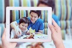 La mamá toma la foto del muchacho asiático y del papá que comen las patatas fritas fotografía de archivo libre de regalías