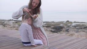 La mamá trenza el pelo de la hija en la playa almacen de metraje de vídeo