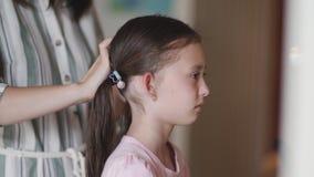 La mamá trenza a la niña infeliz delante de un espejo almacen de metraje de vídeo