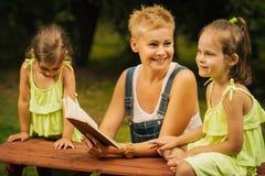 La mamá y dos hijas adorables hablan el uno al otro en el bosque del verano imagen de archivo libre de regalías