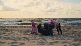 La mamá y dos hijas están jugando en la arena en la playa en la puesta del sol almacen de video