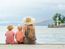 La mamá y dos hijos se sientan en el embarcadero y admiran el mar y las montañas en la distancia Visión posterior fotos de archivo