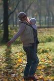 La mamá y el bebé en una honda disfrutan las hojas de otoño que caen Imagen de archivo