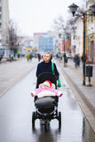 La mamá y el bebé están caminando en la ciudad Imagen de archivo