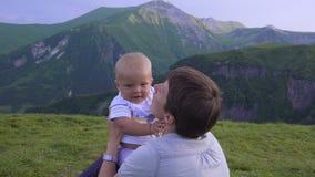 La mamá y el bebé están jugando en las montañas almacen de video
