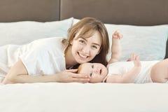 La mamá y el bebé están mirando la cámara que miente en la cama fotografía de archivo libre de regalías