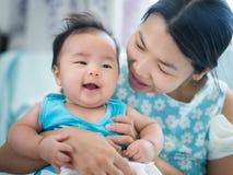 La mamá y el bebé juegan juntos en sitio de la cama imágenes de archivo libres de regalías