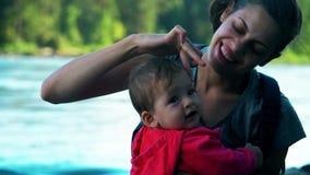 La mamá y el bebé se están sentando y los abrazos en la orilla del río almacen de metraje de vídeo