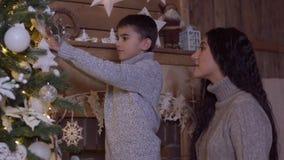 La mamá y el hijo adornan un árbol de navidad que tiene un buen humor 4K metrajes