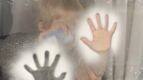 La mamá y el hijo adornan ventanas con nieve artificial metrajes