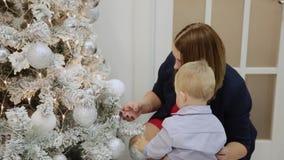 La mamá y el hijo están considerando los juguetes en el árbol de navidad almacen de video