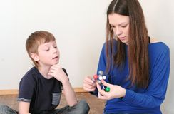 La mamá y el hijo están construyendo modelos de la molécula del sistema plástico coloreado de la construcción Vista lateral fotografía de archivo