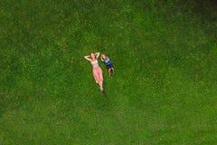 La mamá y el hijo están mintiendo en la hierba en el parque, fotos del abejón, quadracopter fotografía de archivo libre de regalías