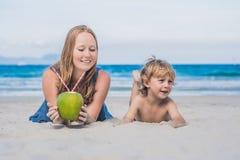La mamá y el hijo gozan de la playa y beben el coco imagen de archivo