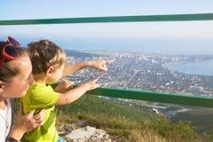 La mamá y el hijo miran la ciudad por el mar de alturas imágenes de archivo libres de regalías