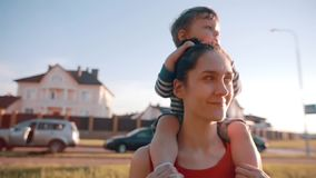 La mamá y el hijo pasan el tiempo junto El niño pequeño lindo se sienta en sus hombros de las mamáes, ella sonríe feliz Sun brill