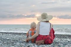 La mamá y el hijo que se sientan en el océano apuntalan Visión desde la parte posterior Foto de archivo