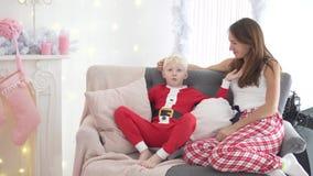 La mamá y el hijo se están sentando en el sofá por el árbol de navidad metrajes