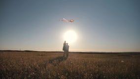 La mamá y el hijo vuelan una cometa en un campo en la puesta del sol metrajes