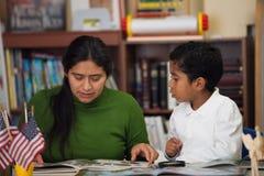 La mamá y el muchacho hispánicos adentro enseñan en casa el ajuste que estudia rocas Foto de archivo