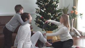 La mamá y el niño dan el regalo de la Navidad al padre que se sienta en el piso por el árbol de navidad Familia joven feliz con almacen de video