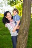 La mamá y el niño ocultan detrás de árbol y de la diversión el tener Foto de archivo