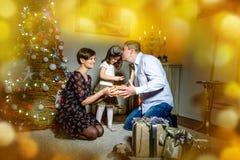 La mamá y el padre dan un pequeño regalo de la Navidad del niño en el fondo del árbol Imágenes de archivo libres de regalías