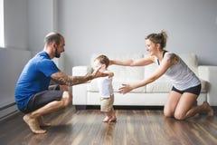 La mamá y el papá alegres ayudan a su hijo a caminar en casa fotos de archivo