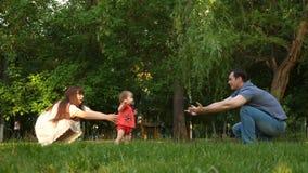 La mamá y el papá aprenden caminar el bebé, niño toma las primeras medidas en césped en parque en el verano almacen de video