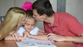 La mamá y el papá calman a un estudiante gritador que ganó primeros dos en escuela