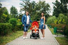 La mamá y el papá caminan en el pakr con un bebé en cochecillo de bebé fotos de archivo