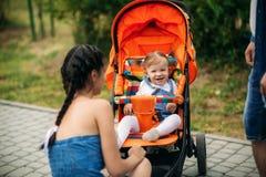 La mamá y el papá caminan en el pakr con un bebé en cochecillo de bebé imagenes de archivo