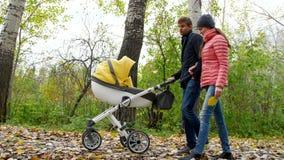 La mamá y el papá están caminando en el bosque con un bebé recién nacido almacen de metraje de vídeo