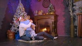 La mamá y el papá felices abrazan a su hijo cerca de la chimenea de la Navidad Cámara lenta almacen de metraje de vídeo