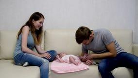 La mamá y el papá se están sentando con una hija en el sofá almacen de metraje de vídeo