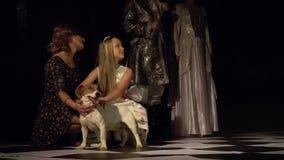 La mamá y la hija acarician al perro que se coloca en un tablero de ajedrez contra la perspectiva del rey y de la reina brillante metrajes