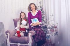 La mamá y la hija alegres se están sentando con los presentes Imagen de archivo libre de regalías