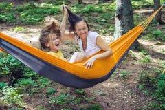 La mamá y la hija alegres se relajan en una hamaca Imágenes de archivo libres de regalías