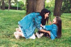 La mamá y la hija en el césped se divierten imagen de archivo libre de regalías