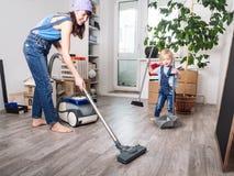 La mamá y la hija en guardapolvos azules del dril de algodón limpiaron en casa y limpiado con la aspiradora fotos de archivo